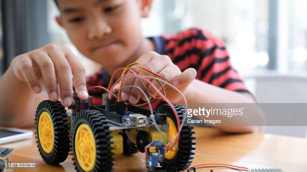 concentrated boy creating robot at lab. - monster truck stock pictures, royalty-free photos & images