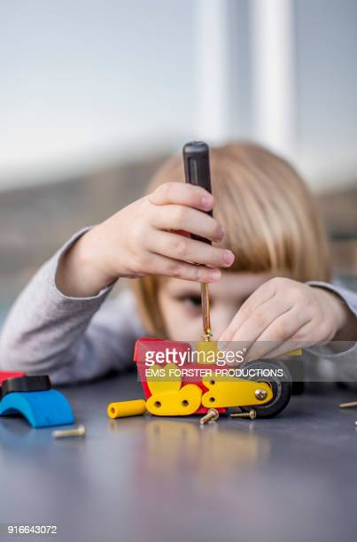 concentrated, cute, little child is playing and screwing with wooden toys