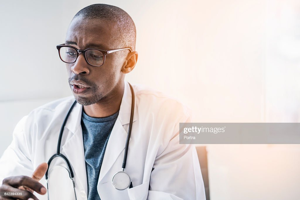 Concentrated doctor in lab coat with stethoscope : Stock Photo