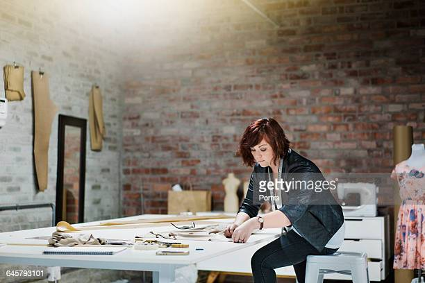 concentrated fashion designer is working in shop - leanincollection working women stock photos and pictures