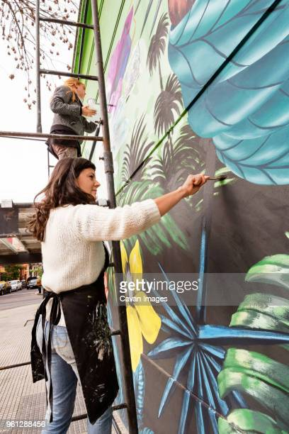concentrated female artists painting mural on wall - peinture murale photos et images de collection