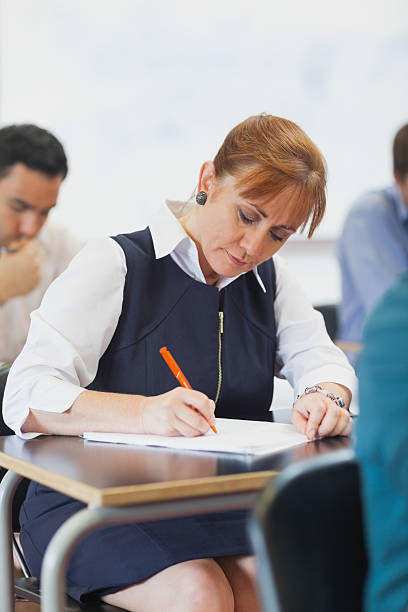 Concentrated female mature student sitting in classroom