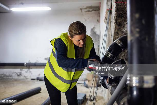 concentrated female plumber sawing pipe at basement - stichsäge stock-fotos und bilder
