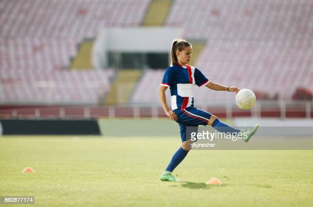 Concentrated female soccer player practicing on the field.