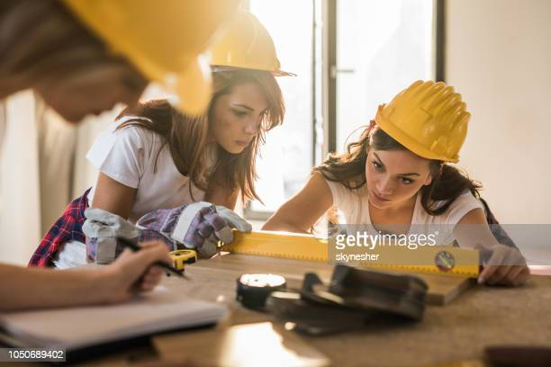 Concentrated female workers using level while working on construction site.