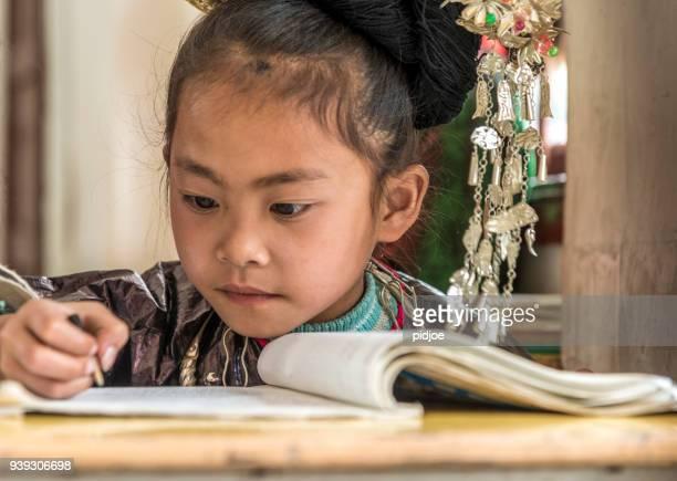 学習者の学校を集中して書きます。離れて見て、選択と集中、小さな村、黄ギャング。」nChild は伝統的な洞服を着ています。ドンは、中国の少数民族です。