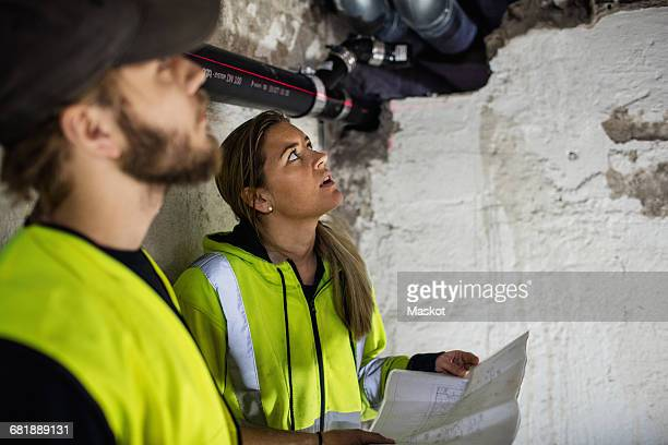 Concentrated male and female plumbers looking up while reading document at basement
