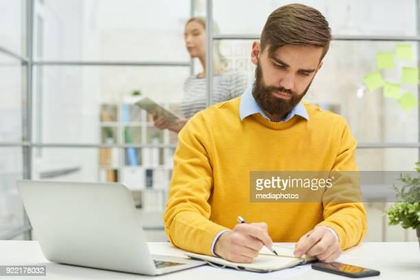 concentrado empregado masculino planejamento cronograma do projeto - atividade móvel - fotografias e filmes do acervo