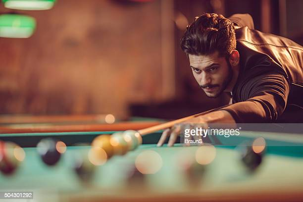 Concentrated man aiming at ball during snooker game.