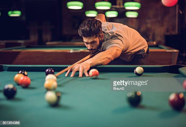 Concentrated man aiming at pool ball while playing snooker.