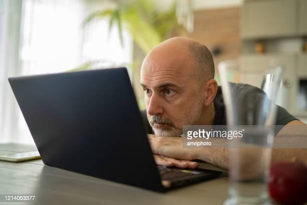 konzentrierter mann, der laptop betrachtet, der während der coronavirus-quarantäne von zu hause aus arbeitet - websurfen stock-fotos und bilder