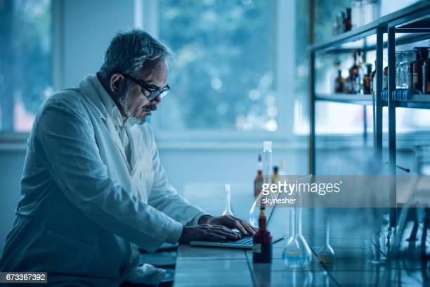 Concentrated mature biochemist working on laptop in a laboratory.