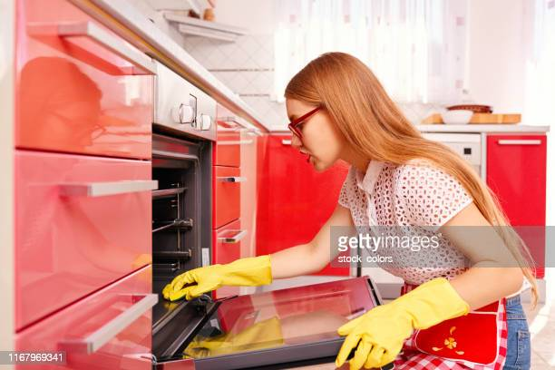 concentrated on cleaning the oven - oven stock pictures, royalty-free photos & images