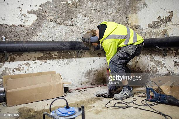 Concentrated plumber drilling floor by pipes in basement