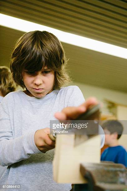 concentrated schoolboy works with wood, sawing, sloyd