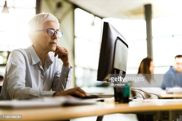 concentrated senior businesswoman working on pc in the office. - examining stock pictures, royalty-free photos & images