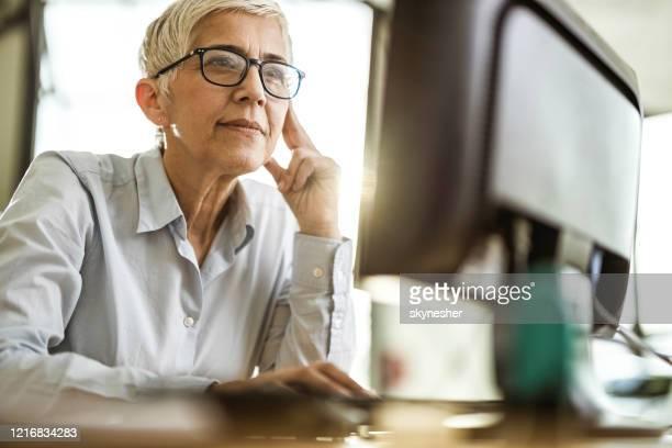 オフィスでpcに取り組む集中シニアビジネスウーマン。 - 銀行支店長 ストックフォトと画像