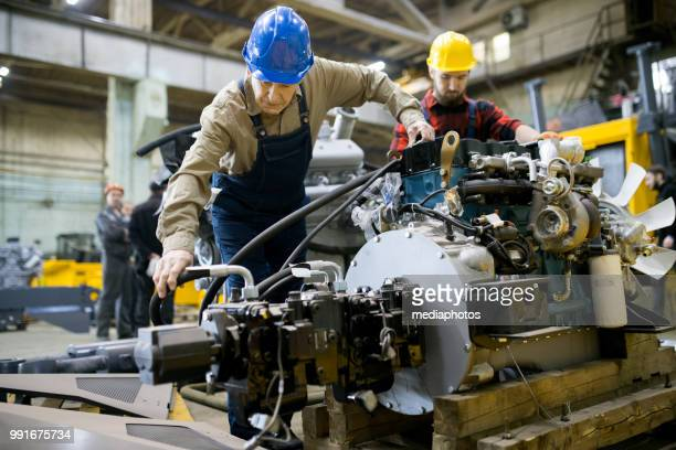 concentrated skilled engineers in hardhats assembling tractor engine while attaching hose together in industrial workshop - motor vehicle stock pictures, royalty-free photos & images