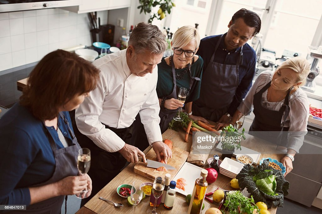 Concentrated students looking at chef cutting salmon in kitchen : Stock Photo
