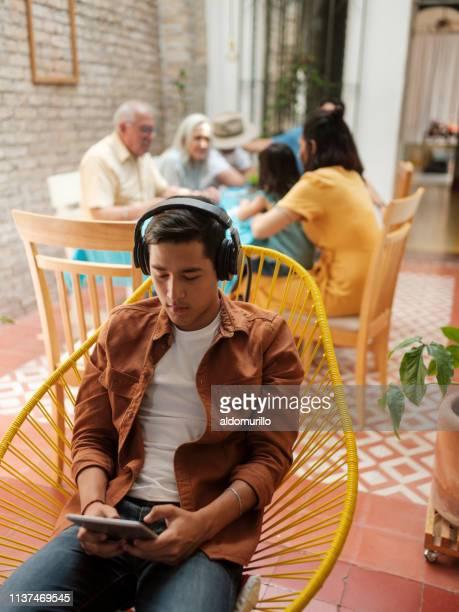 geconcentreerde tiener mexicaanse jongen met behulp van een tablet - nosotroscollection stockfoto's en -beelden