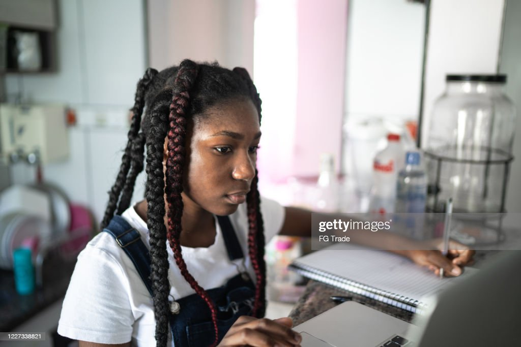 Concentrated teenager using laptop at home : Stock Photo