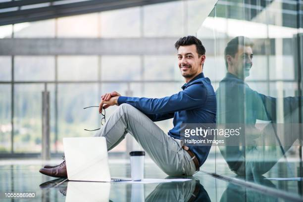 Concentrated young man with laptop sitting on the floor in the modern building, working.