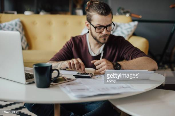 concentrated young student using online banking to pay the bills - bank account stock pictures, royalty-free photos & images