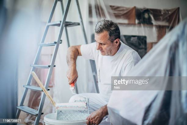 concentrating while decorating - dungarees stock pictures, royalty-free photos & images