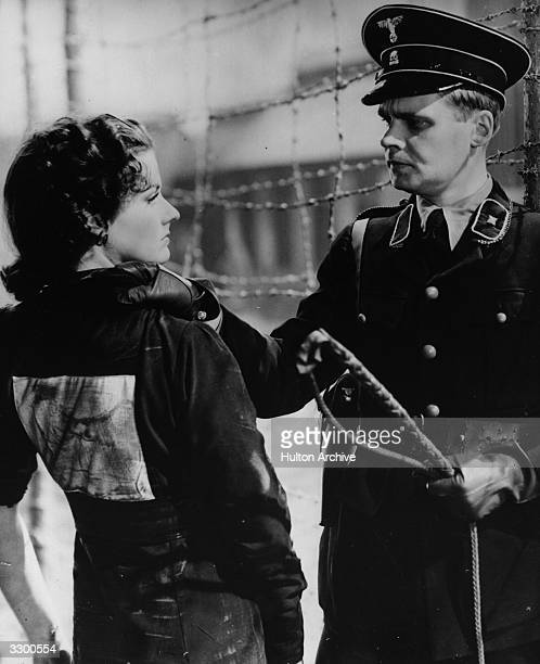 A concentration camp officer threatens Margaret Lockwood with a whip in a scene from the 20th Century Fox film 'Gestapo' aka 'Night Train to Munich'...