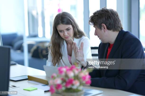 concentration of business talking with partnership isolated over blurred background - femme entre deux hommes photos et images de collection