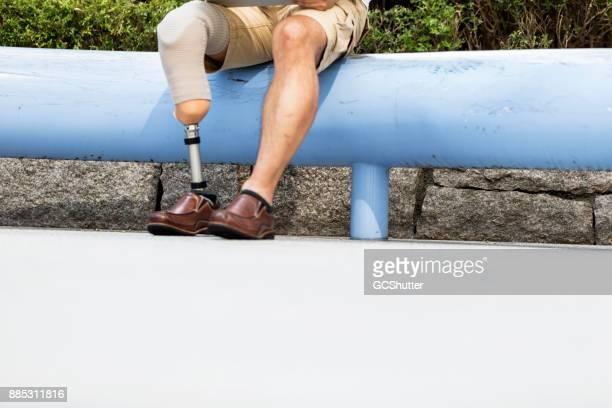 Concept beeld van een man dragen prothetische been en zitten buiten zijn kantoor
