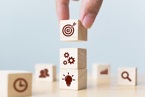 Concept of business strategy and action plan. Businessman hand putting wood cube block on top with icon 1128789418