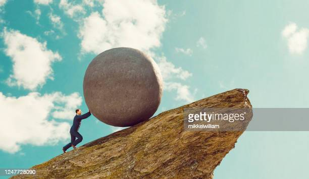 concept of hard work for businessman pushing rock up a hill - over burdened stock pictures, royalty-free photos & images
