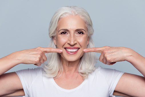 Concept of having strong healthy straight white teeth at old age. Close up portrait of happy with beaming smile female pensioner pointing on her perfect clear white teeth, isolated on gray background 925898340