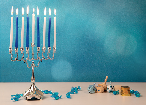concept of jewish religious holiday hanukkah with wooden spinning top toys (dreidel), traditional chandelier menorah and chocolate coins 1188847067