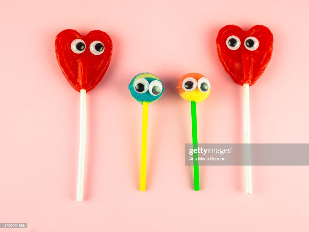 Concept of love and family. Two red heart lollipops with eyes looking at each other and two smaller lollipops : Stock Photo