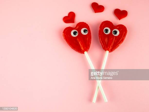 concept of love and romanticism. two red heart lollipops with eyes looking at each other and several red hearts - valentine card stock pictures, royalty-free photos & images