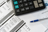 Concept of paying bills. Close up cropped photo with flat lay high angle above top view of object blank calculator and pen