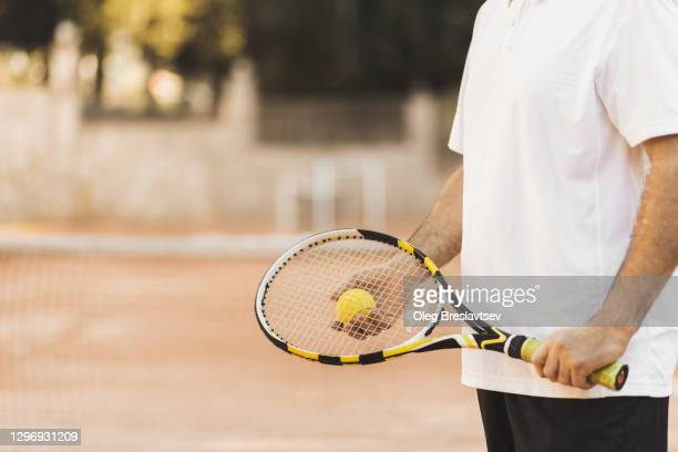 concept of playing tennis game. man holding racket and ball in hand, unrecognizable abstract person - ラケット ストックフォトと画像