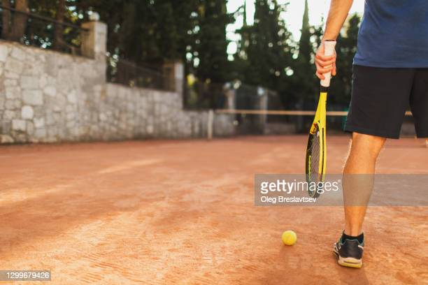 concept of playing tennis game. man holding racket and ball, view from behind - tennis ball stock pictures, royalty-free photos & images