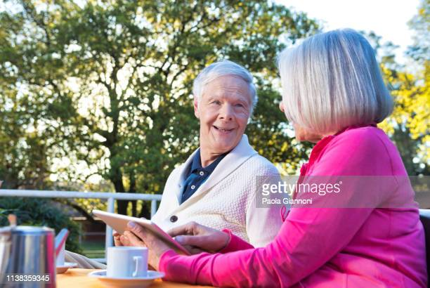 Concept of retirement community. Retired couple using tablet at the pensioner's cafeteria