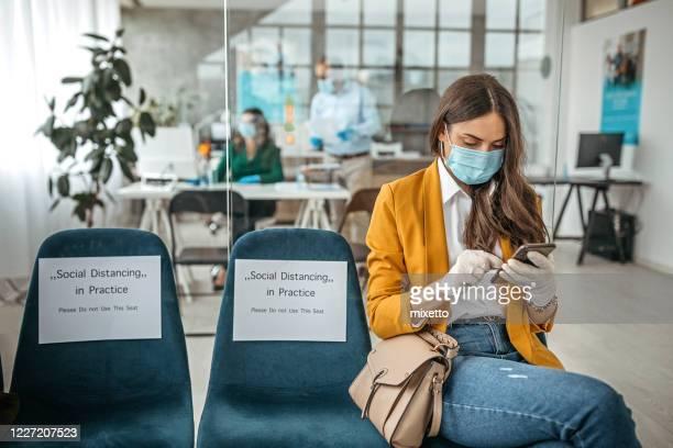 concept van sociale distantiëring om verspreiding van infectieziekten op het werk te voorkomen - beschermend masker werkkleding stockfoto's en -beelden