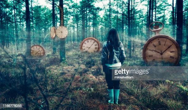 begreppet tid med kvinna i skogen omgiven av stora klockor - dag bildbanksfoton och bilder