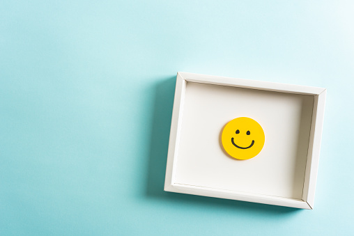 Concept of well-being, well done, feedback, employee recognition award. Happy yellow smiling emoticon face frame hanging on blue background with empty space for text. 1138474232