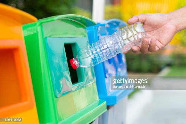 concept recycly:close up hand throwing empty plastic bottle into the trash recycling. - recycling stock pictures, royalty-free photos & images