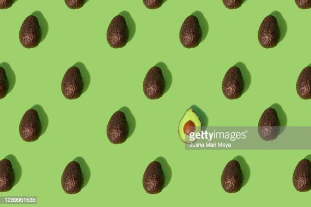 concept stand out from the crowd  large group of whole avocados placed in a repeating pattern where one split in half stands out from the crowd - avocado stock pictures, royalty-free photos & images