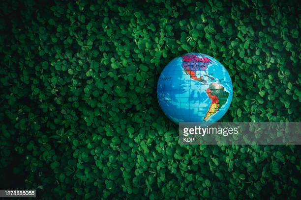 concepts save the world and environmental conservation, global model on field green grass with glowing sunlight. - earth day stock pictures, royalty-free photos & images