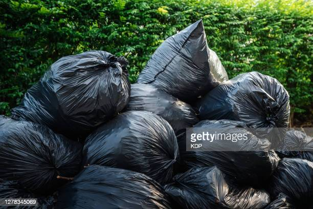concepts save the world and environmental issues, garbage bags stacking storage against green trees backgrounds. waste management - bag stock pictures, royalty-free photos & images