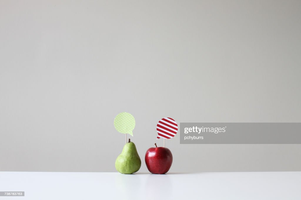 Conceptual apple and pear with speech bubbles : Stock-Foto