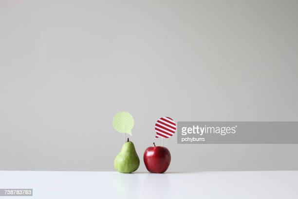 conceptual apple and pear with speech bubbles - dois objetos - fotografias e filmes do acervo